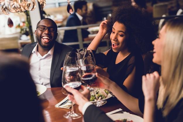 Grupa młodych ludzi pijących wino w restauracji.