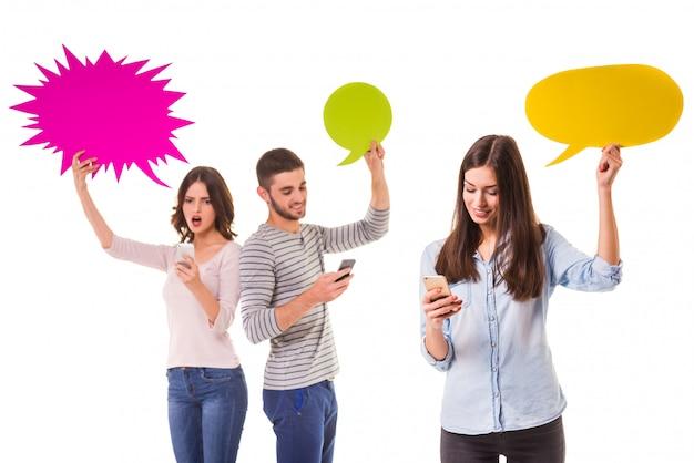 Grupa młodych ludzi posiada kolorowe bańki tekstu.