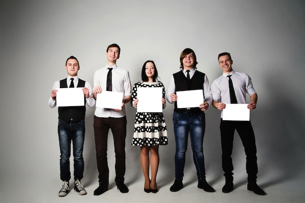 Grupa młodych ludzi posiadających kartki papieru