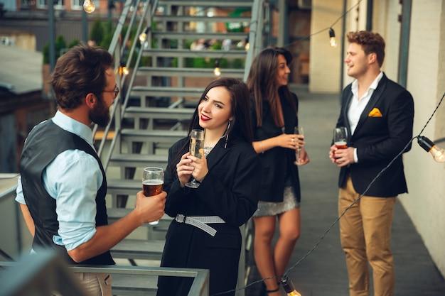 Grupa młodych ludzi rasy kaukaskiej świętujących, wyglądających na szczęśliwych, organizujących imprezę firmową w biurze lub barze