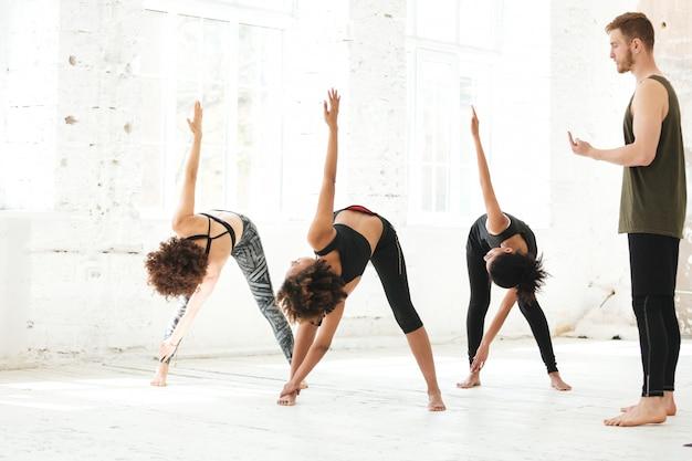 Grupa młodych ludzi robi joga w siłowni