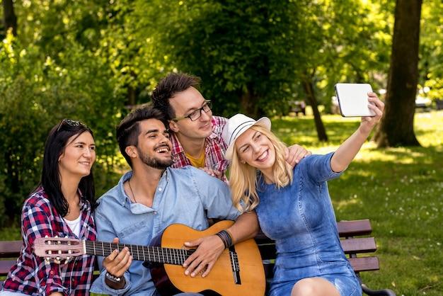 Grupa młodych ludzi robiących selfie i grających na gitarze podczas spędzania czasu w parku