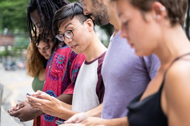 Grupa młodych ludzi różnych narodowości z telefonem komórkowym