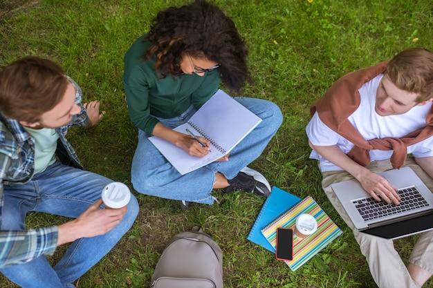 Grupa młodych ludzi siedzących na trawie i przygotowujących się do egzaminów