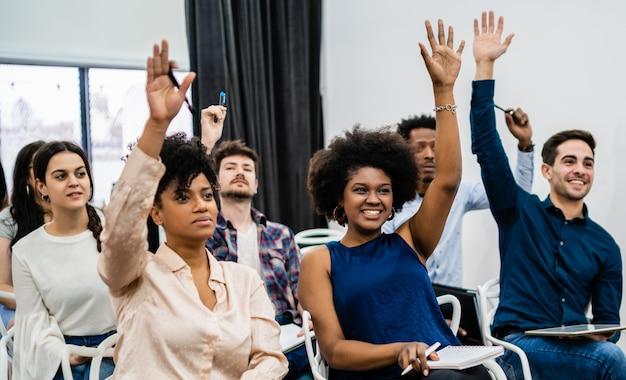 Grupa młodych ludzi siedzi na konferencji razem