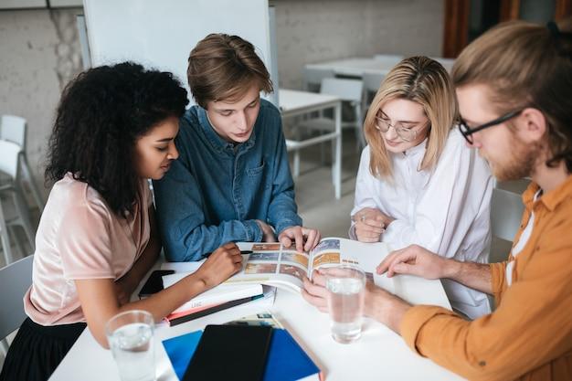 Grupa młodych ludzi siedzi przy stole i pracuje razem. portret dwóch ładnych dziewcząt i dwóch chłopców omawiających coś