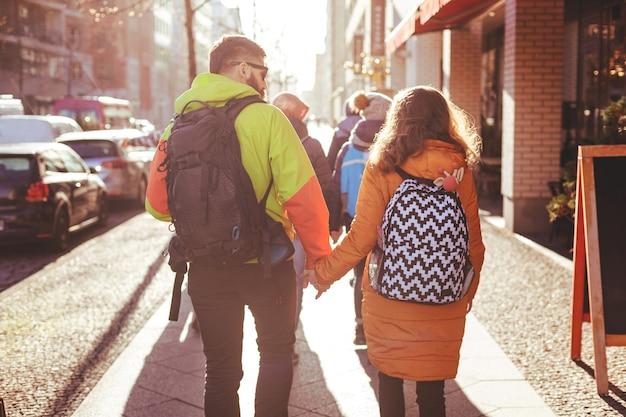 Grupa młodych ludzi spaceruje zimą ulicami berlina. niektóre pary trzymają się za ręce. nakręcony pod światło przy jasnym słońcu