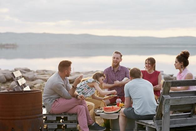 Grupa młodych ludzi spędzających czas nad pięknym jeziorem w letni wieczór, jedząc owoce, rozmawiając i miło spędzając czas