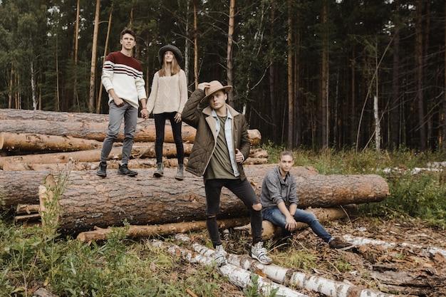 Grupa młodych ludzi stojących na dużych kłodach