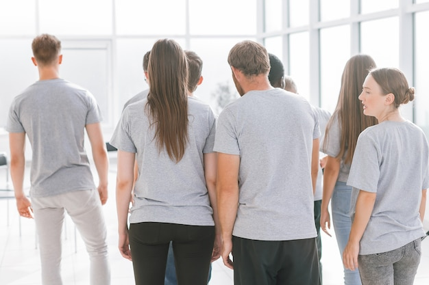 Grupa młodych ludzi stojących w jasnym pokoju