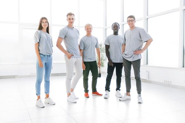 Grupa młodych ludzi stojących w pustym biurze. zdjęcie z miejsca na kopię