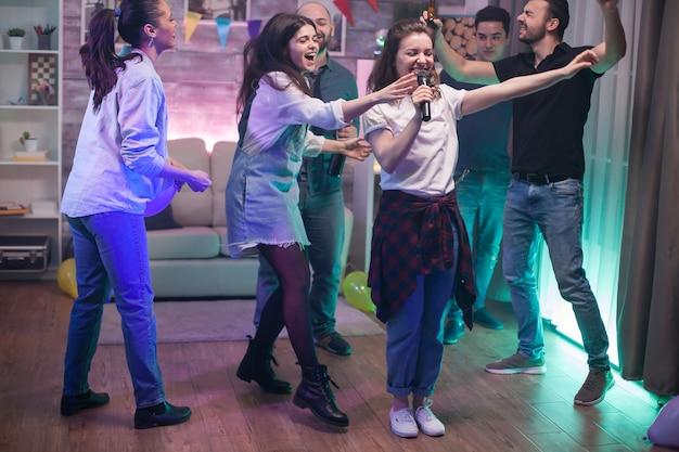 Grupa młodych ludzi tańczących i piękna młoda kobieta śpiewa na mikrofonie.
