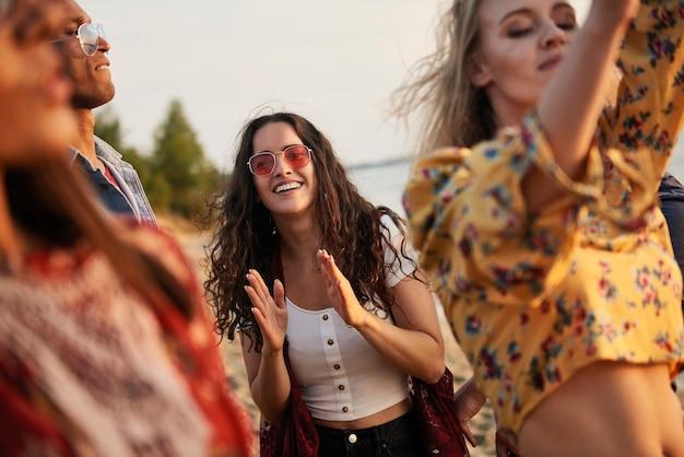 Grupa młodych ludzi tańczących na plaży