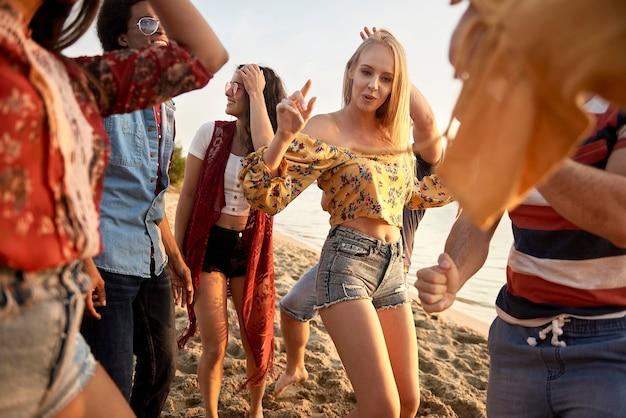 Grupa młodych ludzi tańczących o zachodzie słońca