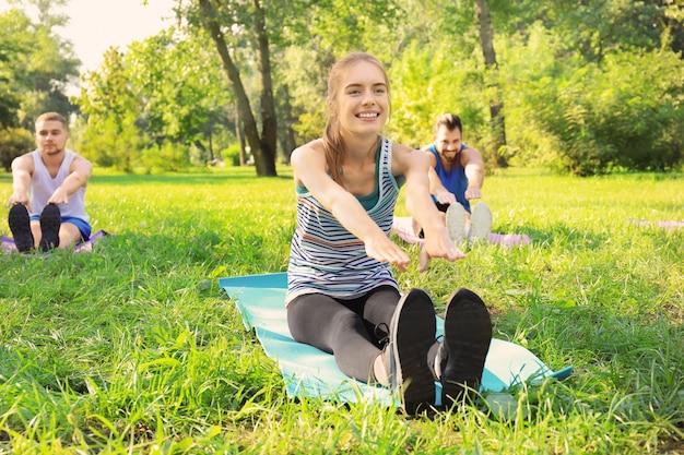 Grupa młodych ludzi trenujących w parku