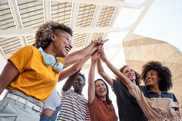Grupa młodych ludzi układających rękę wieloetniczna grupa studentów świętujących na świeżym powietrzu