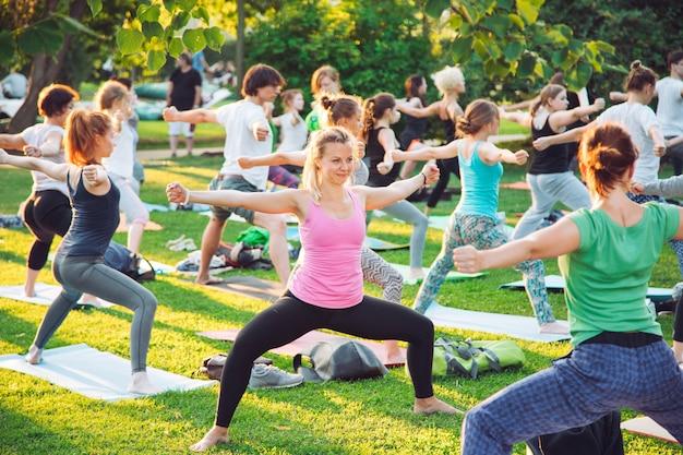 Grupa młodych ludzi uprawia jogę w parku o zachodzie słońca.