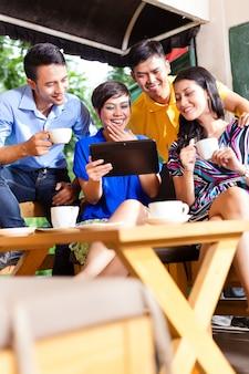 Grupa młodych ludzi w azjatyckiej kawiarni