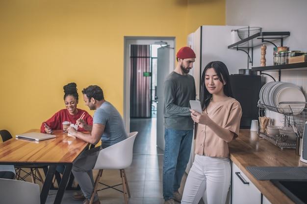 Grupa młodych ludzi w biurowej kuchni