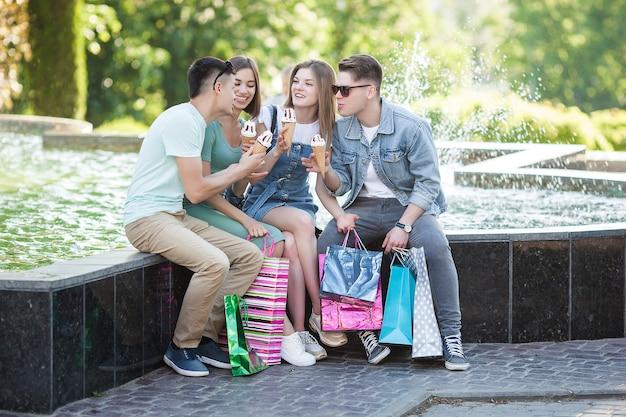 Grupa młodych ludzi wesoły jedzenie lodów i zabawę. kupujący na zewnątrz. ludzie po zakupach. zabawna grupa przyjaciół odpoczywających w pobliżu fontanny.