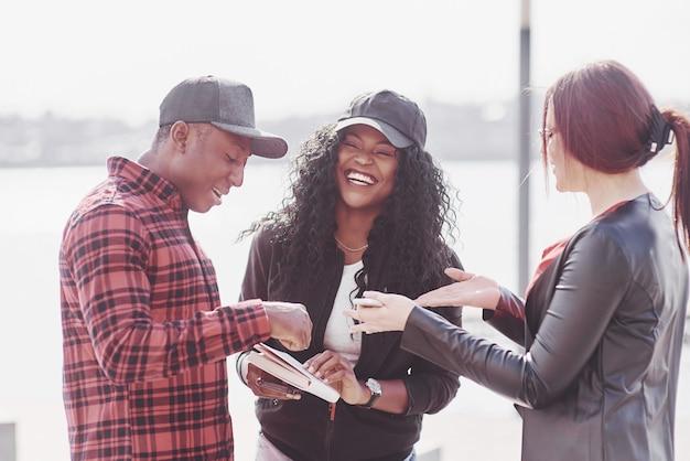 Grupa młodych ludzi wielonarodowych z książką, studenci studiujący na wolnym powietrzu