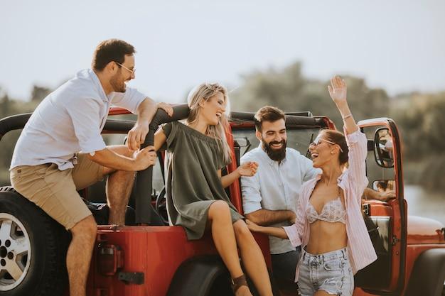 Grupa młodych ludzi zabawy samochodem na świeżym powietrzu w gorący letni dzień
