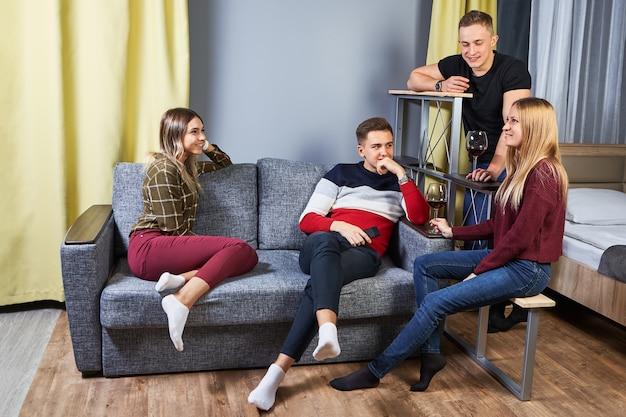 Grupa młodych mężczyzn i kobiet w wieku studenckim siedząc na kanapie w schronisku młodzieżowym.