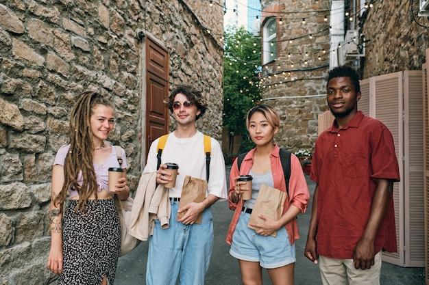 Grupa młodych międzykulturowych przyjaciół z napojami i przekąskami