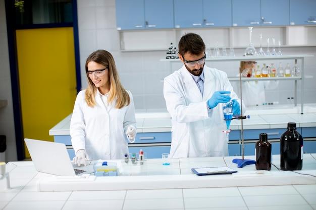 Grupa młodych naukowców analizujących dane chemiczne w laboratorium
