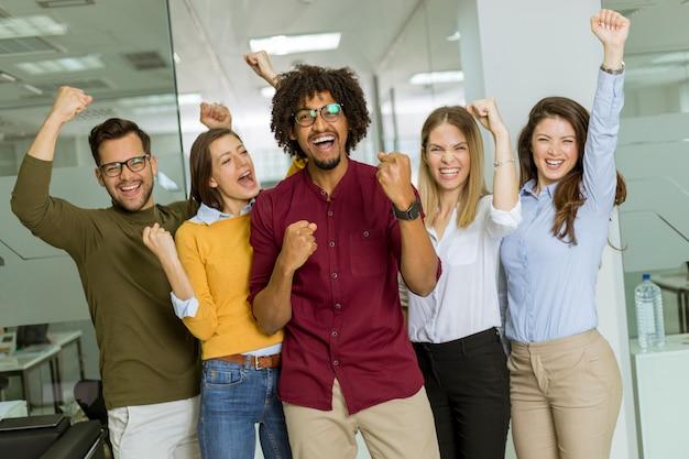 Grupa młodych podekscytowanych ludzi biznesu z rękami w górze stoi w biurze