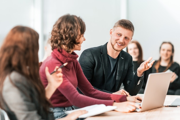 Grupa młodych pracowników siedzi przy biurku. pomysł na biznes