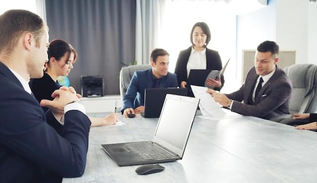 Grupa młodych prawników odnoszących sukcesy biznesmenów komunikujących się ze sobą w sali konferencyjnej podczas pracy nad projektem