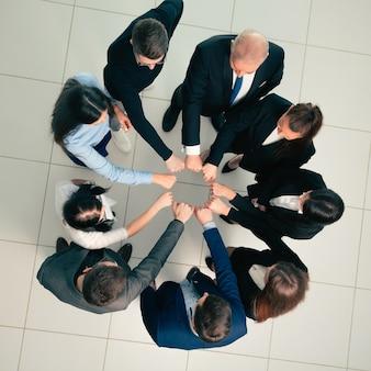 Grupa młodych profesjonalistów stojących w kręgu
