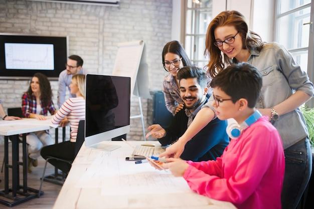 Grupa młodych projektantów patrzących na cyfrowy tablet w biurze
