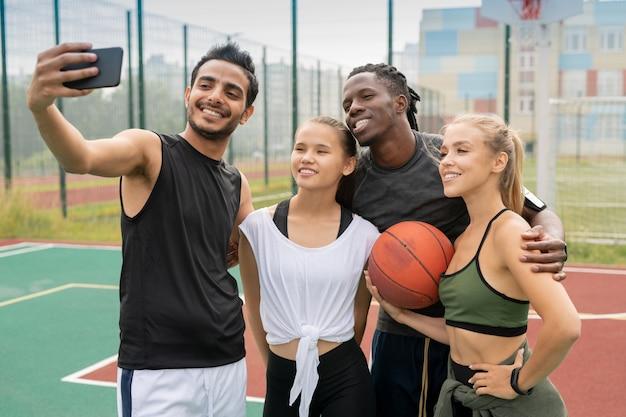 Grupa młodych przyjaciół międzykulturowych w odzieży sportowej robiąc selfie na boisku lub boisku do koszykówki na świeżym powietrzu