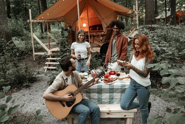 Grupa młodych przyjaciół podróżujących glampingiem w lesie, bawiąc się grając na gitarze i mbira kalimba pieczenie kiełbasek siedząc przy stole w pobliżu namiotu podczas letnich wakacji śmiejąc się spędzać czas