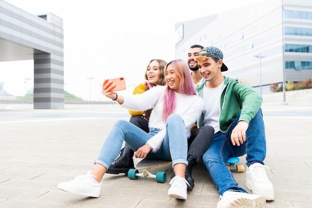 Grupa młodych przyjaciół robi sobie selfie w mieście