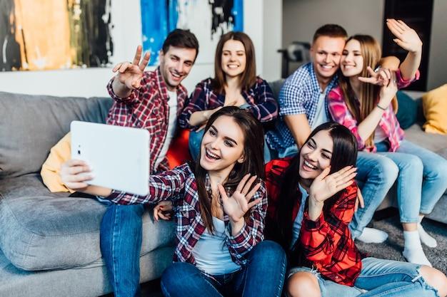 Grupa młodych przyjaciół siedzi w domu na kanapie i rozmawia z rodzicami online