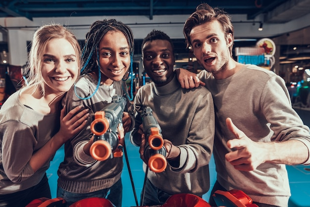 Grupa młodych przyjaciół strzelanie z broni w arcade.