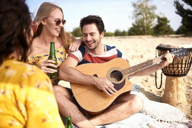 Grupa młodych przyjaciół świetnie się bawi na plaży?