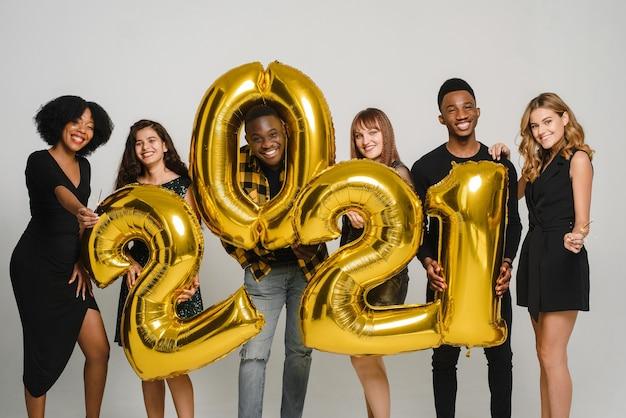 Grupa młodych przyjaciół świętuje boże narodzenie. młodzi, różnorodni ludzie mają numery 2021