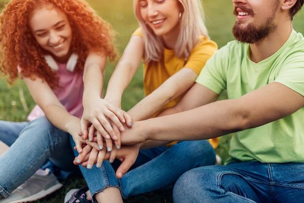 Grupa młodych przyjaciół, trzymając się za ręce razem jako zespół