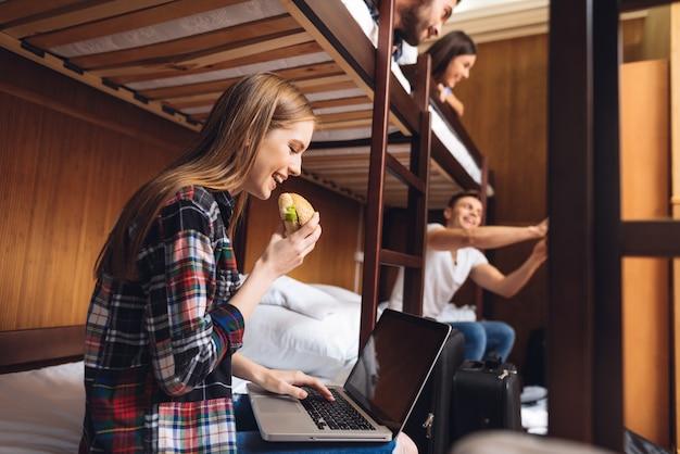 Grupa młodych przyjaciół w koszulkach w kratę porusza się w hostelu.