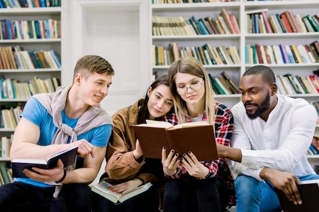 Grupa młodych przyjaciół wielorasowych studentów, siedząc w bibliotece kampusu, czytając książki podczas przygotowań do egzaminów, testu lub pracy domowej