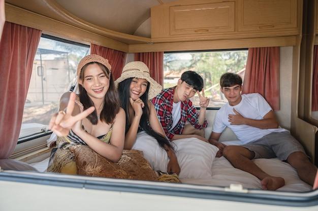 Grupa młodych przyjaciół z azji, zabawy wewnątrz samochodu kempingowego w weekend