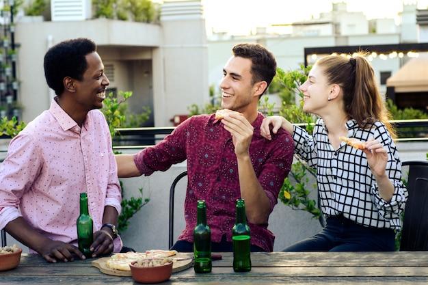 Grupa młodych przyjaciół z pizzy i butelek napoju
