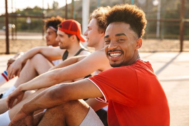 Grupa młodych radosnych mężczyzn wieloetnicznych koszykarzy