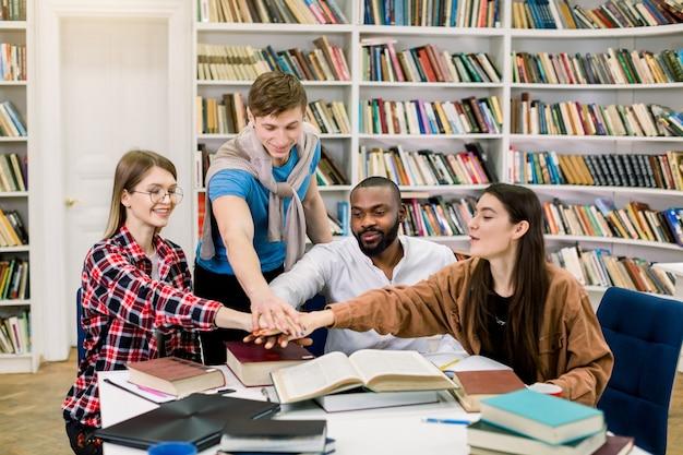 Grupa młodych radosnych wielorasowych studentów współpracujących przy projekcie, siedzących przy stole w bibliotece