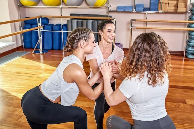 Grupa młodych sportowców ćwiczących lekcję jogi z instruktorem, ćwicząca warrior two, ćwicząca, sesja w sali na całej długości, studenci trenujący w klubie, studio