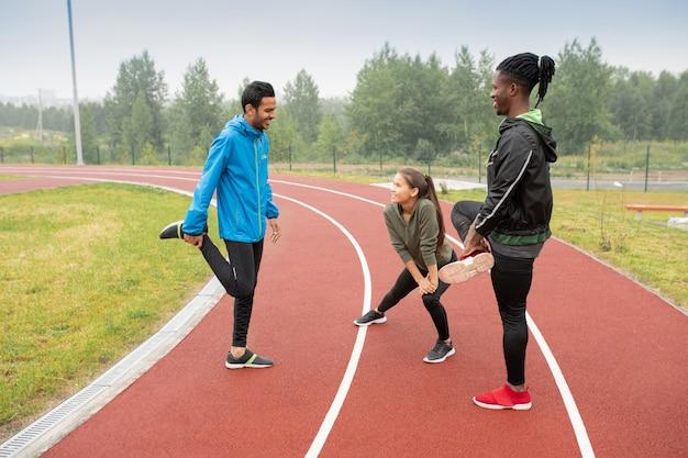 Grupa młodych sportowców międzykulturowych uprawiająca ćwiczenia rozgrzewające na torach wyścigowych przygotowujących się do maratonu na stadionie